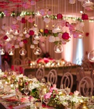 Wedding reception flower print table with gold vessel orbs candles rose suspended from ceiling