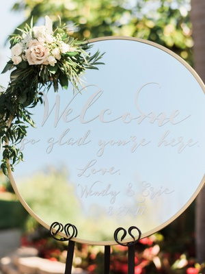 wedding ceremony round mirror welcome sign we're so glad you're here flowers and greenery on top