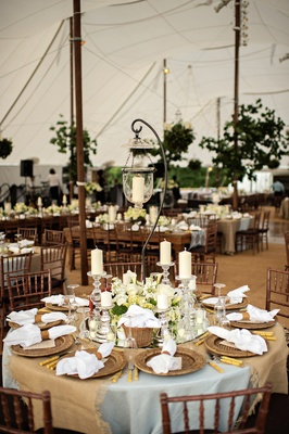 Tented wedding reception table with light blue tablecloth, taupe fabric, hanging lantern, candles