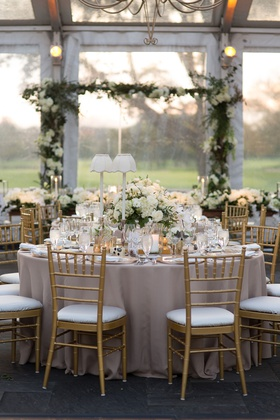 wedding reception clear tent white table lamps gold chairs white greenery centerpiece design
