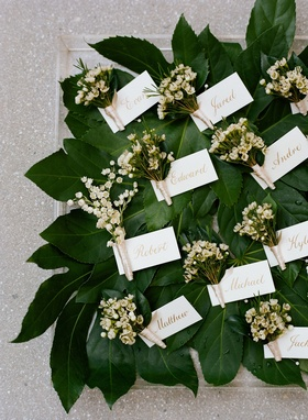 Lily of the valley groomsmen boutonnieres on top of greenery leaves tags with groomsmen names