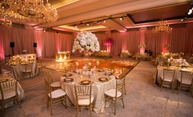 hotel ballroom wedding with pipe and drape with pink uplighting, gold chiavari chairs, tall florals