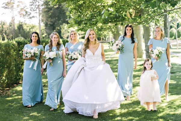 Bridesmaids in robin's egg blue holding bouquets with bride holding up dress flower girl