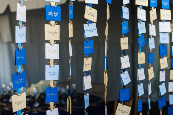 Gold and blue seating card assignments on ribbon