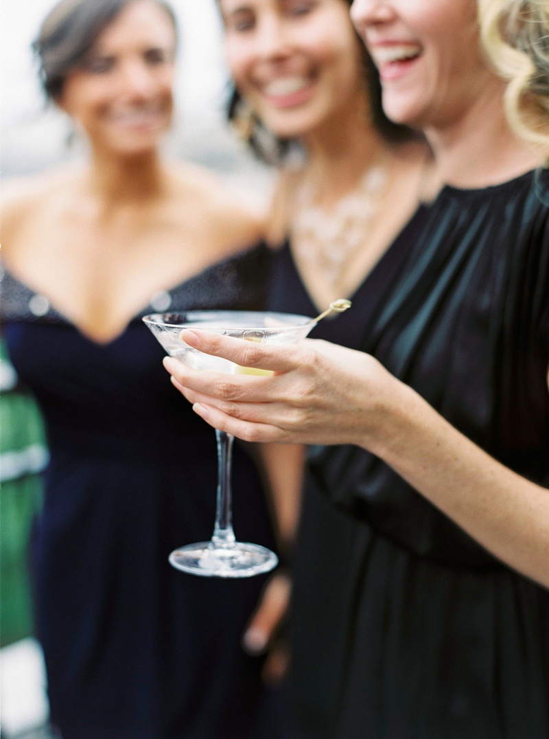 Wedding guest in black dress holding martini glass with olive at cocktail hour reception