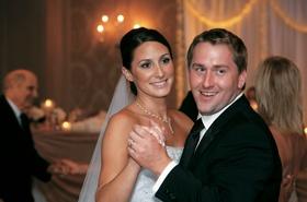 Bride and groom dance in reception ballroom