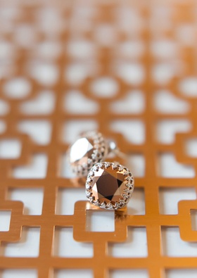 copper jewel earrings on top of a geometric design in the same color