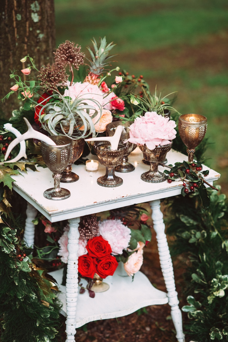 Outdoor wedding reception table with red roses, pink peonies, airplants, antlers in goblets