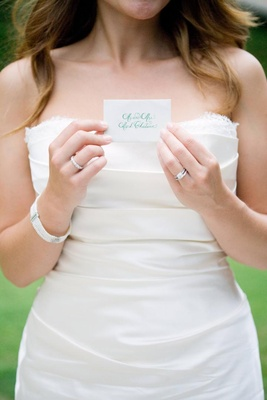 Bride holding white escort card with turquoise calligraphy