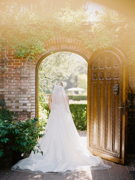 bride in martina liana a-line gown, cathedral veil