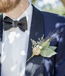 close up picture of grooms navy blue tuxedo and his wheat boutonniere with green leaves wildflowers