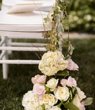 White ceremony chair entwined with vines and flowers