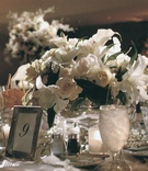 Lilies and roses in short vase and table number in silver frame