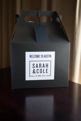 Black cardboard box with white monogram sticker