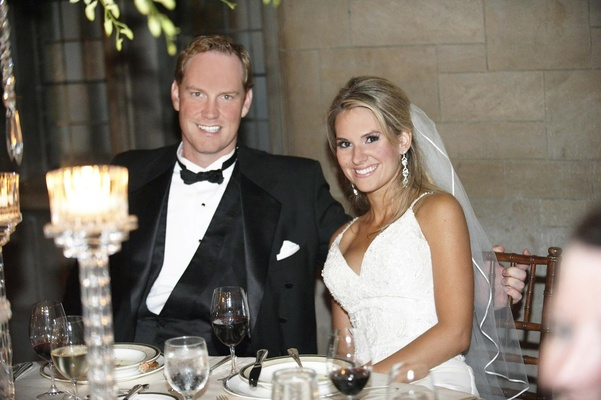 Bride in a spaghetti strap gown sits with groom in black tuxedo at reception