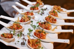 Wedding cocktail hour with tray of ceviche in ceramic spoons tortilla strip & greenery garnish