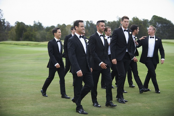 Groom with friends in tuxedos on grass