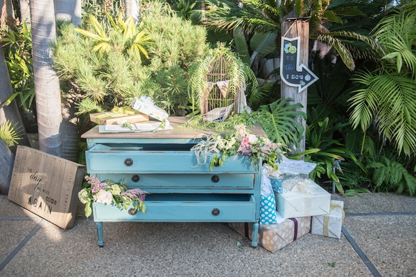 Garden wedding with a vintage light blue dresser for gifts, gold birdcage, pink, white flowers