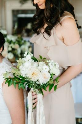 Bridesmaid in tan dress holding greenery white rose stephanotis blossom bouquet