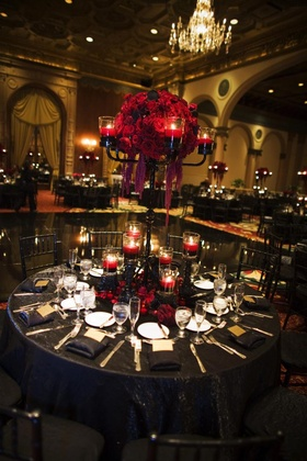Wedding reception table with black candelabra with red candles floating in red water and red roses
