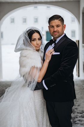 bride in sparkle wedding dress with fur wrap and hood cape groom with black gloves and tuxedo snow