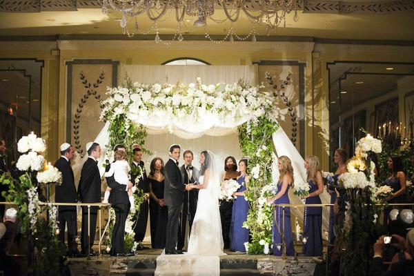 Bride and groom under white and green chuppah