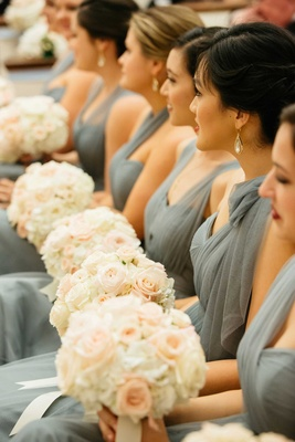 Bridesmaids in grey-blue dresses with round white and pink wedding flower bouquets