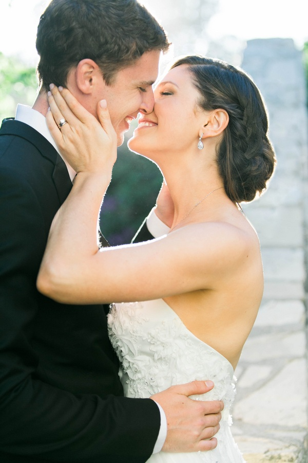 bride with drop earrings and strapless Winnie Couture bridal gown kisses groom