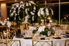 round wedding reception table black napkin gold chairs low centerpiece greenery eucalyptus orchid