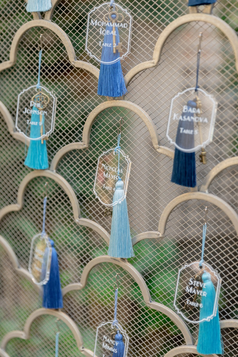 lucite escort cards attached to tassels in different shades of blue