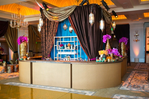 Moroccan-style engagement party with brown, patterned, gold draping behind bar with diamond design