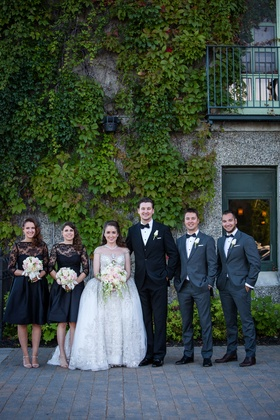 Bride in kleinfeld bridal beaded ball gown with bridesmaids in lace cocktail dresses three quarter