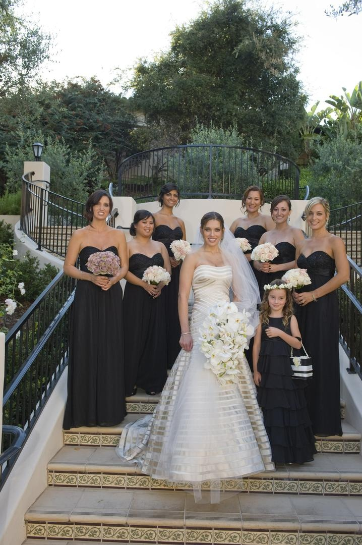 Bride in a strapless Vera Wang gown with bridesmaids in long strapless black dresses
