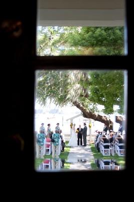 Artistic photo of wedding ceremony through window