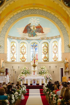 Wedding ceremony at church pretty altar arch stained glass white pink flowers aisle runner