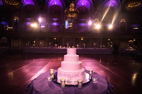 Four layer wedding cake on dance floor at wedding with purple lighting