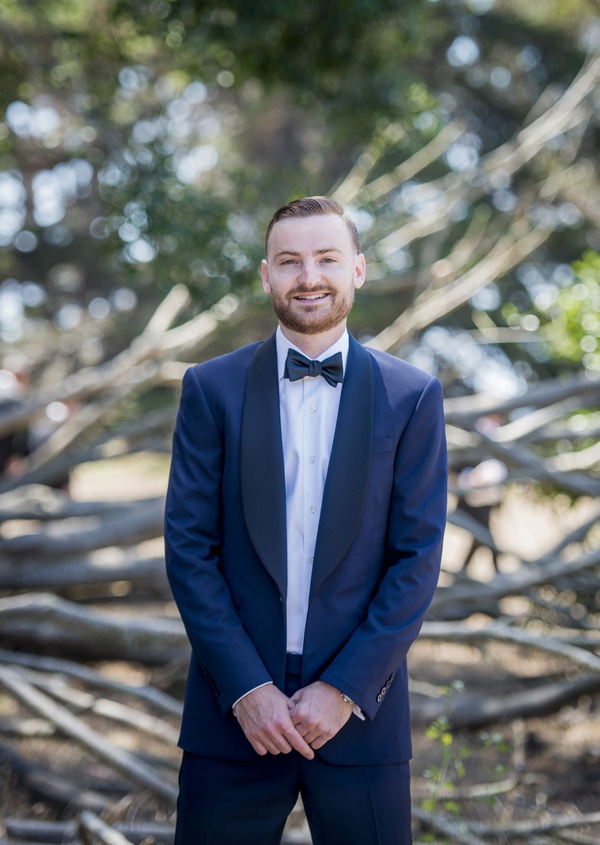 groom in navy blue tuxedo and bowtie stands in forest in santa barbara california