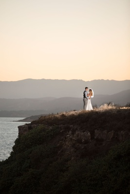 Bride and groom couple location portrait shot reception hair down sleek dress on cliff in California