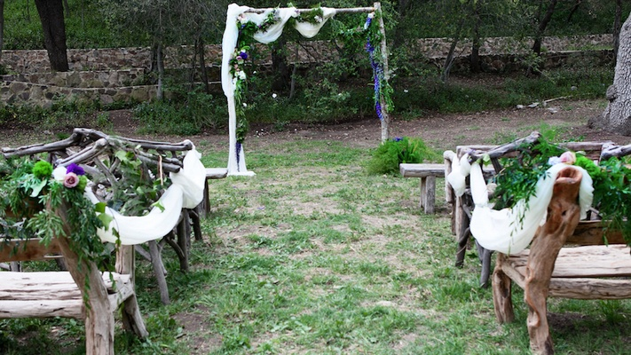 Outdoor wedding ceremony at the Oak Canyon Ranch with guests benches made of wood planks and branche
