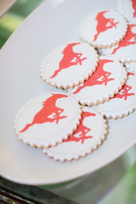White cookies with scallop edges and red galloping horse