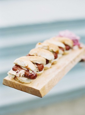 Miniature hot dog buns and hot dogs with topping served on wood board