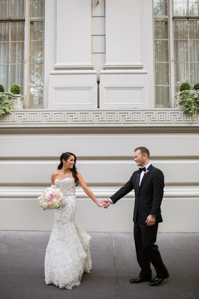 Couple in wedding attire on sidewalk
