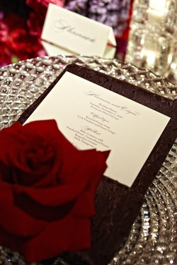 Red rose at wedding place setting and cut glass plate