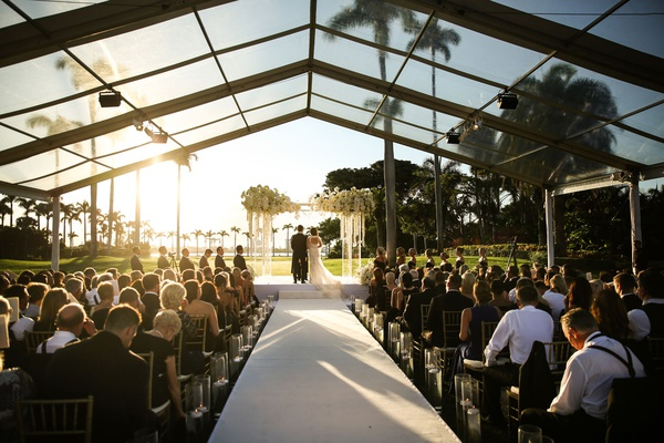 bride and groom under arch acrylic lucite white flowers guests in gold chairs clear top tent over