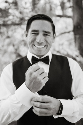 black and white photo of groom smiling with black vest bow tie adjusting cuff links