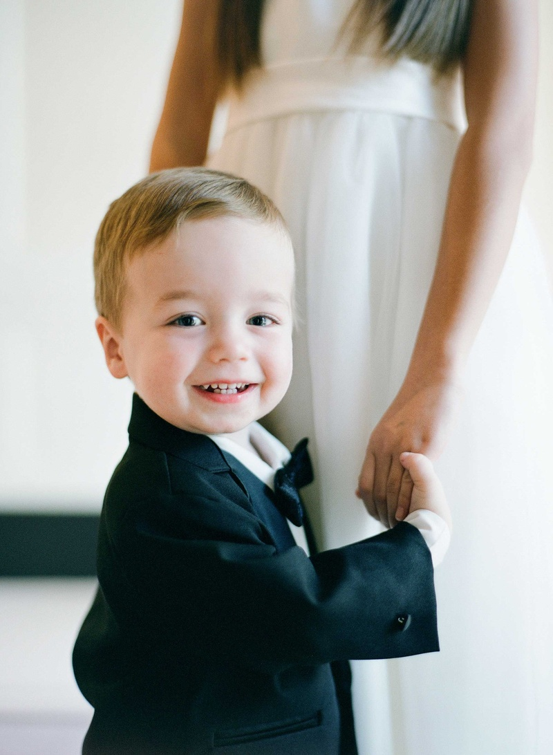 Flower girl holding hand of ring bearer who smiles at camera in bow tie and suit