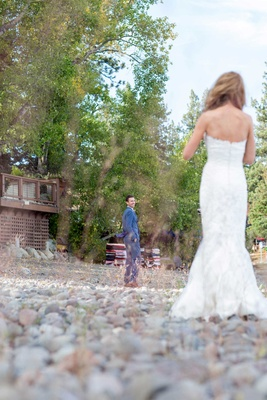 groom turns around to see his bride during first look blue suit white dress pebbles forest