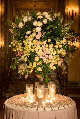 Gold escort cards and candles with large arrangement