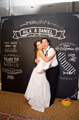 bride and groom hugging, photobooth chalkboard design step and repeat