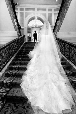 black and white photo of bride in vera wang walking up stairs to groom in hugo boss